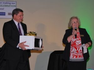 Terry White, GA Food, presents Sandi Narron, Neighborly Director of Marketing with one of the 50 microwaves for 50 Meals on Wheels clients for Neighborly's 50 years